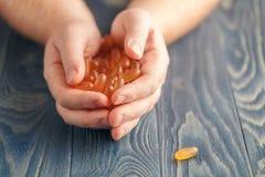 Hög av preventivpillerar i manhänder på tabellen fotografering för bildbyråer
