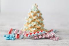 Hög av preventivpillerar under julträd royaltyfri fotografi