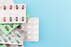 Hög av preventivpillerblåsor på läkarundersökningblåttbakgrund Royaltyfria Foton