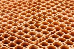 Hög av röda ihåliga tegelstenar med stora hål som bildar en geometrisk modell för upprepning Arkivfoto