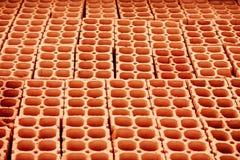 Hög av röda ihåliga tegelstenar med stora hål som bildar linjer, i att upprepa den geometriska modellen Royaltyfri Foto