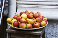 Hög av röda och gula äpplen på maträtt Arkivfoto