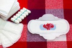 Hög av sanitära mjuka block för menstruation med röda pärlor och bomullstampongen för kvinnahygienskydd Kritiska dagar för kvinna Royaltyfri Fotografi