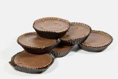Hög av sex bruna choklader i skyddande legitimationshandlingar Arkivbild