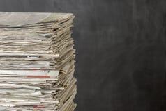 Hög av tidningar på en mörk bakgrund Royaltyfri Bild