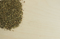 Hög av torkade Basil Flakes på Wood bakgrund arkivfoton