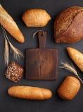 Hög av utsmyckat bröd runt om träskärbräda fotografering för bildbyråer