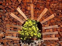 Hög av vedträt med vasen av gula blommor royaltyfri foto