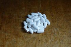 Hög av vita preventivpillerar på trätabellen royaltyfri bild