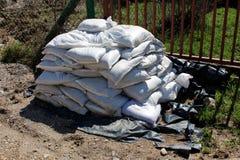 Hög av vita sandpåsar på den svarta nylonräkningen som i fall att förbereds för flodskydd av nödläget fotografering för bildbyråer