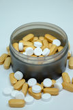 Hög av vitaminer i svart flaska på vit bakgrund Royaltyfri Bild