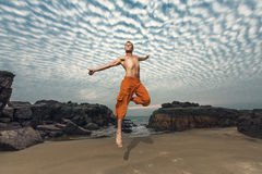 Hög banhoppning för ung man på stranden Arkivbild