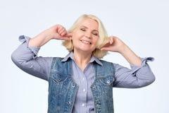 Hög blond kvinna med leende och skämtsamt uttryck på hennes framsida som pluggar öron royaltyfria foton