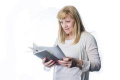 Hög blond kvinna som läser en tidskrift Royaltyfria Bilder