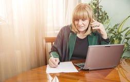 Hög blond kvinna som ner skriver en beställning royaltyfri foto