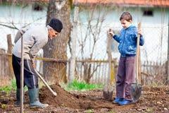 Hög bonde med sonsonen i trädgården Royaltyfria Bilder