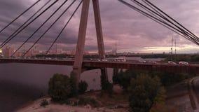 Hög bro med triangulära trossar över Dniproen på impressionistsolnedgången stock video
