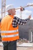 Hög byggmästare i hardhats som utomhus pekar royaltyfria bilder