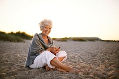 Hög caucasian kvinna med mobiltelefonen på stranden royaltyfri bild