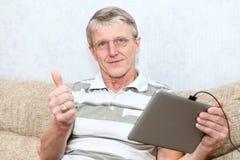 Hög Caucasian man i exponeringsglas med tabletdatoren Arkivfoto