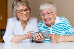 Hög dam som använder den smarta telefonen med hennes moder arkivfoton