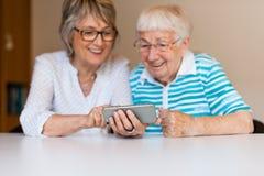 Hög dam som använder den smarta telefonen med hennes moder arkivbilder
