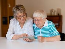 Hög dam som använder den smarta telefonen med hennes moder royaltyfri fotografi