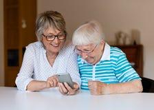 Hög dam som använder den smarta telefonen med hennes moder royaltyfria foton
