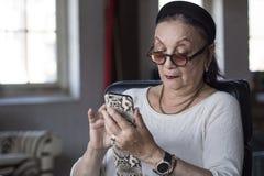 Hög dam som använder hennes smarta telefon Royaltyfri Foto