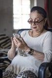 Hög dam som använder hennes smarta telefon Arkivfoto