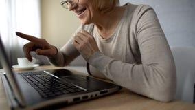 Hög dam som glädjas för att tala till barn i internet som ser bärbar datorskärmen royaltyfria foton