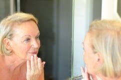 Hög dam som kontrollerar hennes hud i spegeln Arkivfoto