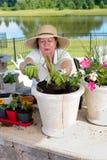 Hög dam som lägger in upp houseplants Arkivbild