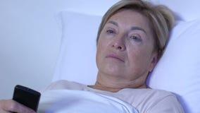 Hög dam som sovande faller med den avlägsna kontrollanten för TV i händer, hemafton stock video
