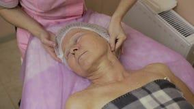 Hög dam som tycker om massage i skönhetsalong arkivfilmer