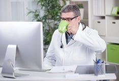 Hög doktor i kontoret som arbetar på datoren en drinkcof arkivbilder