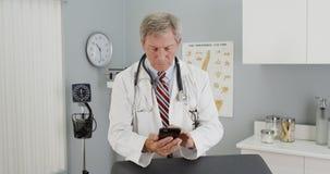 Hög doktor som använder smartphonen i kontoret Arkivfoto