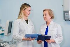 Hög doktor som talar med assistentanseende för ung kvinna i det gynekologiska kontoret med stol och lampan på royaltyfri fotografi