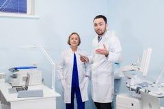 Hög doktor som talar med assistentanseende för ung man i det gynekologiska kontoret med stol och lampan på arkivbilder