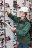 Hög elektriker med ett skruvmejsel- och ledningsnätdiagram i hans handanseende nära en elektrisk sköld Royaltyfria Bilder