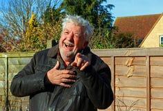 Hög eller äldre man som skrattar och pekar på kameran Arkivbild