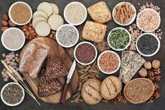 Hög fiberhälsokost med hela kornbröd och rullar, hel vetepasta, korn, muttrar, frö, havremjöl, havre, smällare, korn royaltyfri bild