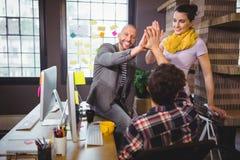 Hög fiving för lyckliga coworkers royaltyfri fotografi