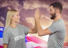 Hög fiving för par mot amerikanska flaggan Royaltyfri Foto