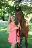 Hög flicka för nätt blond högstadium som är utomhus- med hästen Royaltyfri Bild