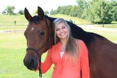 Hög flicka för nätt blond högstadium som är utomhus- med hästen Arkivfoto