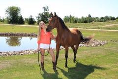 Hög flicka för nätt blond högstadium som är utomhus- med hästen Royaltyfri Fotografi
