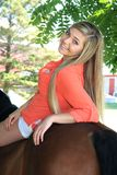 Hög flicka för nätt blond högstadium som är utomhus- med hästen Arkivbilder
