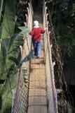 Hög fotvandrare på en hängande bro Arkivbilder
