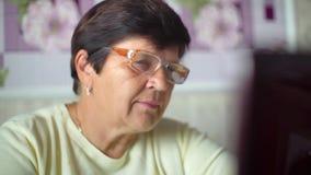 Hög gammal kvinna i glasögon som surfar internet på den hemmastadda closeupen för bärbar dator arkivfilmer